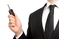 Den isolerade affärsmannen passar in innehav en nyckel- bil Fotografering för Bildbyråer