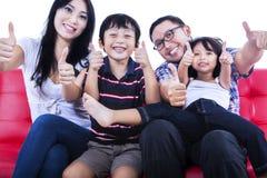 Den isolerade asiatiska familjvisningen tummar upp Royaltyfria Bilder