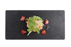 Den isolerade för sikten av Diced laxsallad med avokadot, tomaten, löken, chili och koriander tjänade som i svart rektangelstenpl Arkivbilder