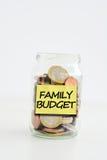 Den isolerade glass kruset med etiketten för familjbudgeten fyllde med mynt fotografering för bildbyråer