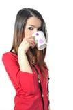 Den isolerade härliga unga flickan som dricker kaffe rånar förbi, på vit bakgrund Arkivfoton