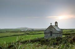 Den isolerade kapellet för St Non'sen med solen som ställer in bak den i Pembrokeshire, Wales arkivbilder