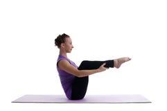 Den isolerade kvinnan sitter i yogaasana på rubber mattt Arkivfoto