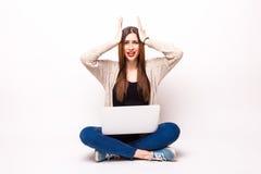 Den isolerade studion sköt av en tillfälligt klädd ung vuxen kvinna som stirrar på hennes bärbar dator Royaltyfri Foto