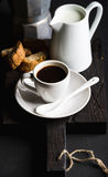 Den italienska kaffeuppsättningen för frukostkopp av varm espresso, creamer med mjölkar, cantucci- och mokakrukan på mörkt lantli Arkivfoton