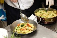 Den italienska kocken förbereder pasta royaltyfria foton