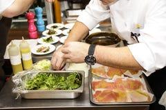 Den italienska kocken förbereder sallad royaltyfri fotografi