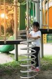 Den Ittle flickan klättrar upp på vårformstege Royaltyfri Bild