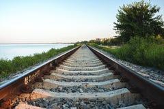 Den järnväg linjen längs kusten av breda flodmynningen av Yeisken royaltyfri bild