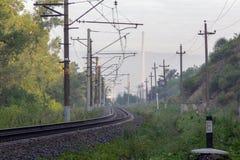 Den järnväg springen till och med höstskogen till fabrikskärnan royaltyfria foton