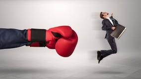 Den jätte- handen ger en spark till en småföretagare royaltyfri bild