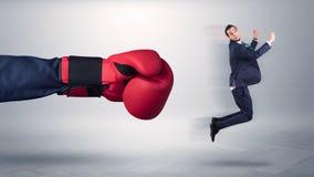 Den jätte- handen ger en spark till en småföretagare royaltyfri fotografi