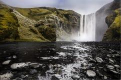 Den jätte- skogafossvattenfallet blir den djupfrysta floden med svart vaggar jordning Royaltyfri Foto