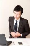 Den japanska affärsmannen lider från magknip Arkivbild
