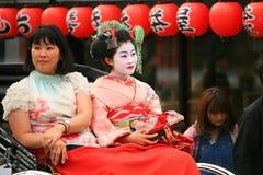 Den japanska flickan klär den traditionella kimonoen Arkivbilder