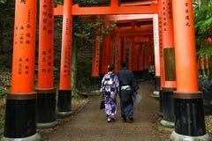 Den japanska geishaen och partnern på den Fushimi Inari relikskrin arbeta i trädgården i Kyoto Arkivbild