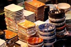 Den japanska handgjorda keramiska disken är visat till salu i det Doguyasuji gallerit, Osaka, Japan Arkivfoto