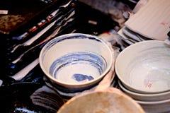 Den japanska handgjorda keramiska disken är visat till salu i det Doguyasuji gallerit, Osaka, Japan Royaltyfri Bild