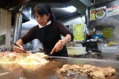 Den japanska kocken förbereder den berömda okonomiyakien för gästerna in Arkivfoton