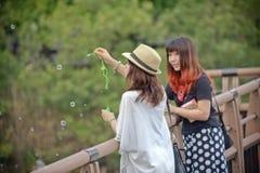 Den japanska kvinnan är avslappnande i en parkera Royaltyfria Bilder