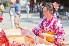 Den japanska kvinnan försöker hennes lycka, genom att agna den lyckliga förmögenhetpappersfisken Royaltyfri Bild
