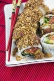 Den japanska sushi och röda pinnar ligger på den vita plattan Royaltyfri Fotografi
