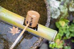 Den japanska träreningskopan i en van vid chozubachi- eller vattenhandfat sköljer händerna i japanska tempel Arkivfoton