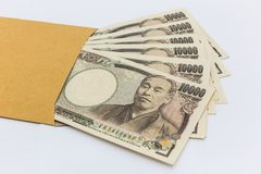 Den japanska yen för sedel 10.000 i det bruna kuvertet för ger sig och affärsframgång och shopping Arkivbild