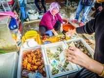 Den Jeju kvinnan förbereder rå skaldjur för att tjäna som till hennes kund Fotografering för Bildbyråer