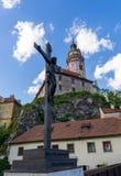 Den Jesus skulpturen av Cesky Krumlov med slotten i backgrou arkivbilder