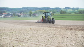 Den jordbruks- traktoren odlar fältet stock video