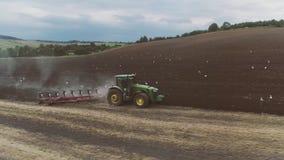 Den jordbruks- traktoren plogar ett stort fält arkivfilmer