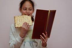 Den judiska flickan läser påskhögtidhaggadahen och ätamatzahen royaltyfri fotografi