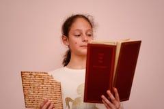 Den judiska flickan läser påskhögtidhaggadahen och ätamatzahen arkivbild