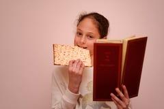 Den judiska flickan läser påskhögtidhaggadahen och ätamatzahen arkivfoto
