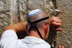 Den judiska mannen ber på den västra väggen i Jerusalem Royaltyfri Foto