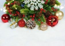 Den julkransen, garneringar och gåvan kura ihop sig i snö Arkivbild