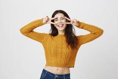Den känslobetonade lyckliga caucasian kvinnliga hållande segergesten nära synar, medan le i huvudsak och uttrycka positiva sinnes royaltyfria foton