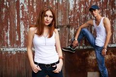 Den känslobetonade ståenden av ett stilfullt kopplar ihop i jeans som står nära trä royaltyfri fotografi