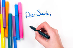 Den kära jultomten undertecknar med en hand på en vitbok med olika kulöra pennor Royaltyfri Bild