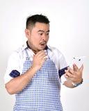 Den köpmanAsian mannen i vit- och blåttförkläde känner sig förvånad eller upphetsad, när få goda nyheter från anslutningsinternet Arkivfoto
