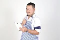 Den köpmanAsian mannen i vit- och blåttförkläde känner sig förvånad eller upphetsad, när få goda nyheter från anslutningsinternet Royaltyfria Bilder