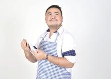 Den köpmanAsian mannen i vit- och blåttförkläde känner sig förvånad eller upphetsad, när få goda nyheter från anslutningsinternet Arkivbilder