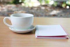 Den kaffekoppen och anteckningsboken förläggas på en brunt trätabell och H royaltyfri foto