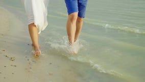 Den kala foten av en man och en kvinna promenerar sanden längs havet Ferie tillsammans i vändkretsarna steadicamskott stock video