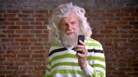 Den kalla caucasian höga mannen med stort vitt lockigt hår och det trevliga skägget har den videopd appellen och talar i stillhet lager videofilmer