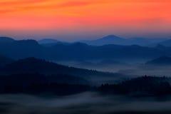 Den kalla dimmiga dimmiga morgonen med skymningsoluppgång i en nedgångdal av bohemmet Schweiz parkerar Kullar med dimma, landskap Arkivbild