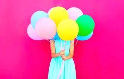 Den kalla flickan är skinn hennes huvud färgrika ballonger för en luft som har gyckel arkivbilder