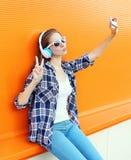 Den kalla flickan gör självståenden på smartphonen lyssnar musik i hörlurar över apelsinen royaltyfri bild