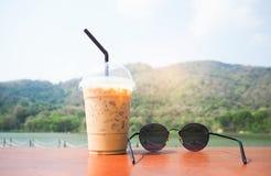 Den kalla kaffe och solglasögon förläggas på tabellen Arkivfoto